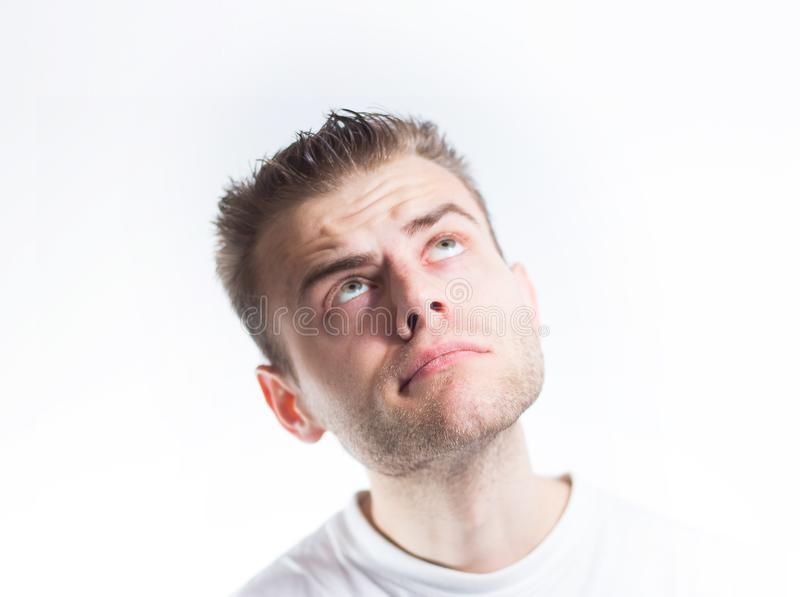 Mannen i en vit T-tröja ser upp på en vit bakgrund royaltyfria bilder