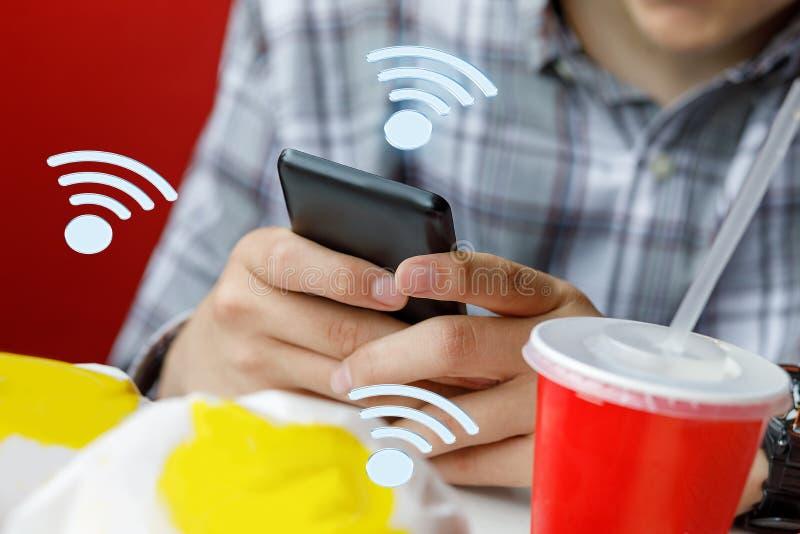 Mannen i ett kafé väljer wifi för att förbinda royaltyfri foto