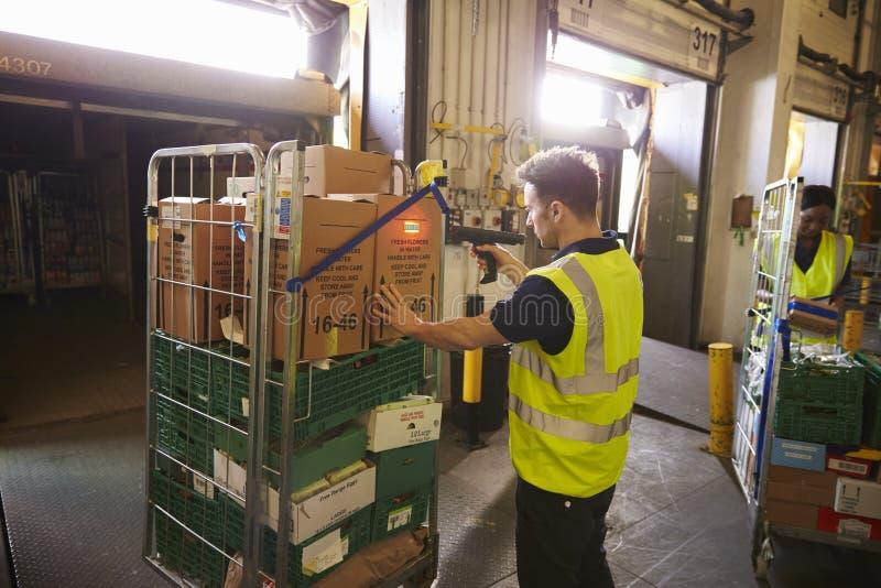 Mannen i ett lager rymmer och avläser en ask för leverans royaltyfria bilder