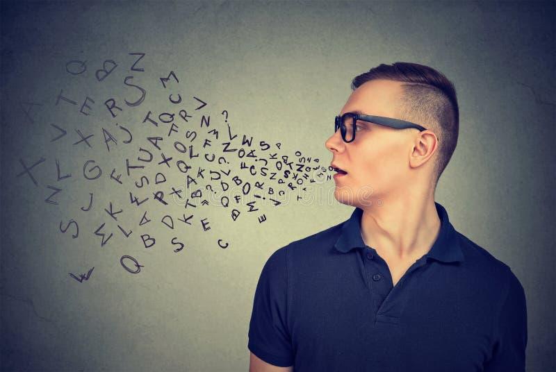 Mannen i exponeringsglas som talar med alfabet, märker att komma ut ur hans mun svart telefon för kommunikationsbegreppsmottagare arkivfoto