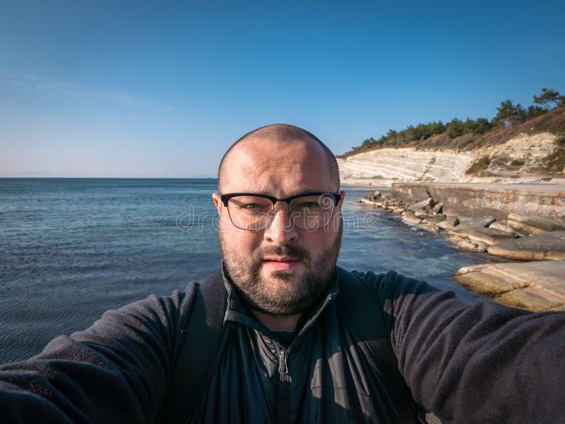 Mannen i exponeringsglas tar selfie på havsstranden och vaggar bakgrund, loppbegrepp arkivfoton