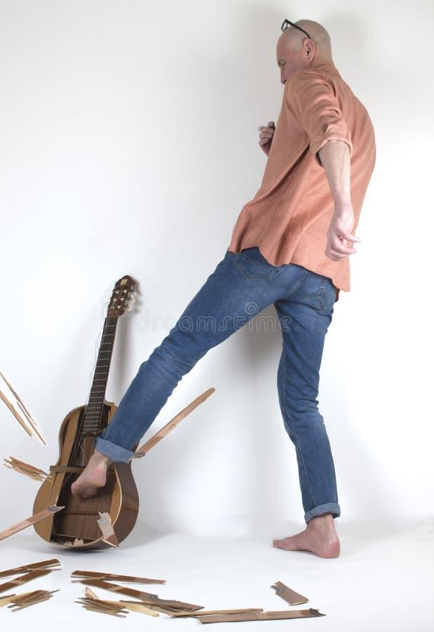 Mannen i förtvivlan som bryter gitarren vid hans ben royaltyfri foto