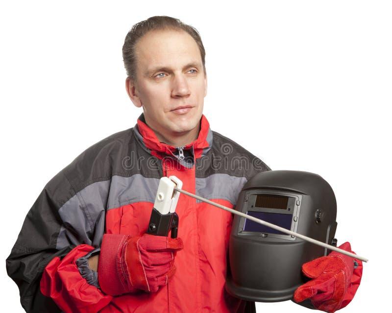 Mannen i funktionsduglig kläder och en weldermaskering med en elektrod royaltyfria bilder