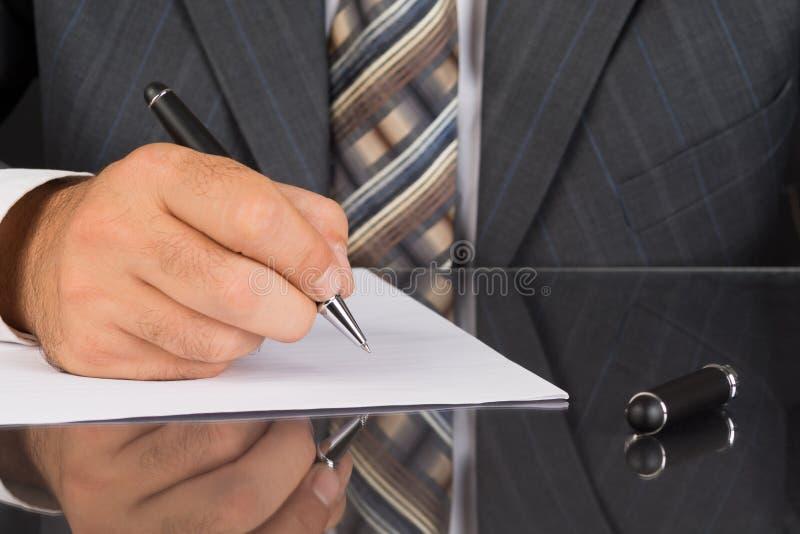 Mannen i grå färger passar håll en metallpenna fotografering för bildbyråer