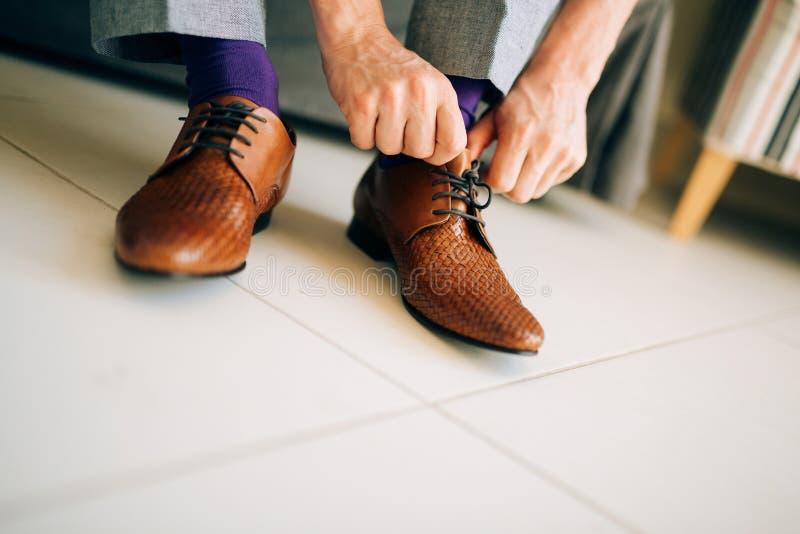 Mannen i grå färger slappnar av och purpurfärgade skor för en klänningsockabrunt med royaltyfri bild
