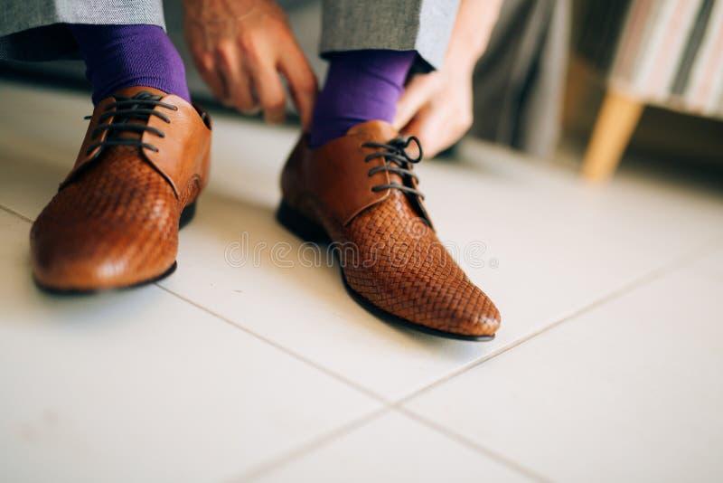 Mannen i grå färger slappnar av och purpurfärgade skor för en klänningsockabrunt med arkivbild