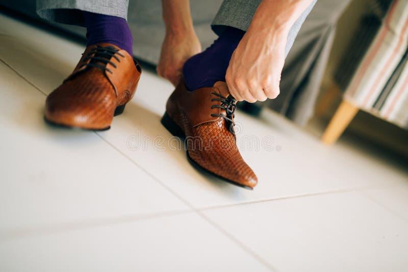 Mannen i grå färger slappnar av och purpurfärgade skor för en klänningsockabrunt med royaltyfria foton