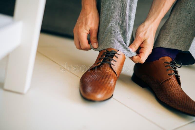Mannen i grå färger slappnar av och purpurfärgade skor för en klänningsockabrunt med royaltyfri fotografi