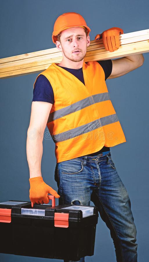 Mannen i hjälm, den hårda hatten rymmer toolboxen och trästrålar, grå bakgrund Snickare inredningssnickare, jobbare, byggmästare  arkivfoto