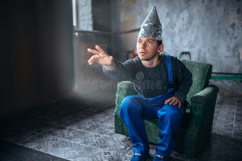 Mannen i hjälm för aluminum folie når ut till TV:N royaltyfri foto