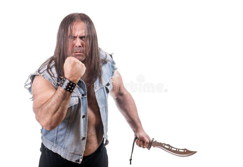 Mannen i jeansomslag hotar med näven och kniven royaltyfri fotografi