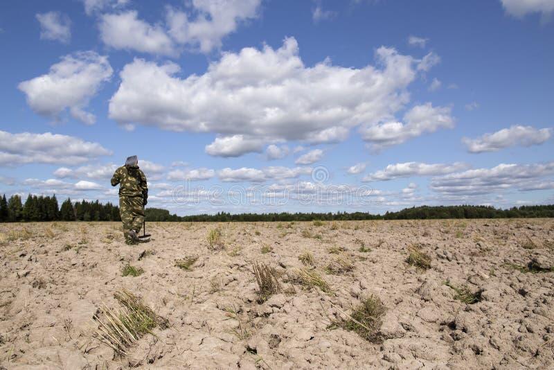 Mannen i kamouflage bär en skyffel på hans skuldra och söka efterskatten genom att använda en metalldetektor på fältet på en bakg royaltyfria bilder