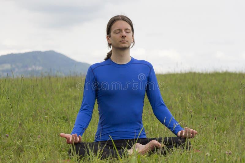 Mannen i lotusblomma poserar att meditera under yoga utomhus arkivfoto
