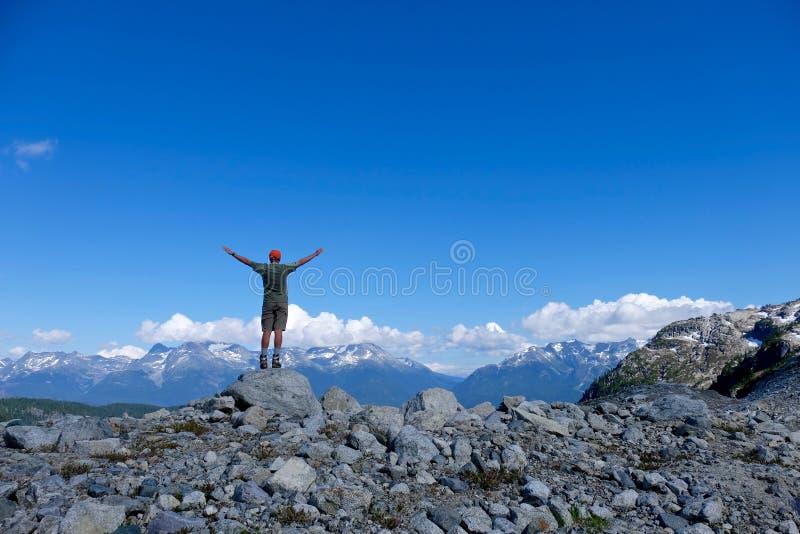 Mannen i lyckat poserar på bergöverkant fotografering för bildbyråer
