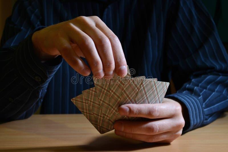 Mannen i mörker som rymmer en uppsättning av spela kort och, väljer ett av dem, strategiskt konkurrensbegrepp för affär fotografering för bildbyråer
