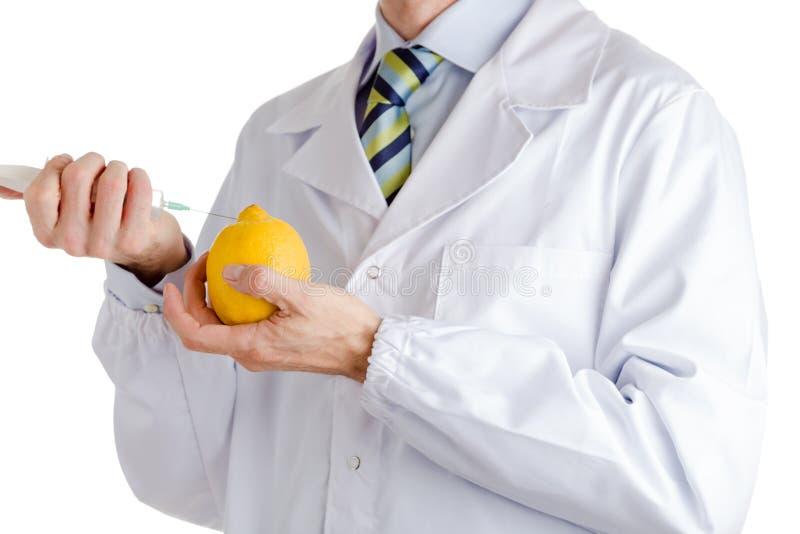 Mannen i medicinskt vitt lag gör en injektion för att gulna citronen arkivfoto