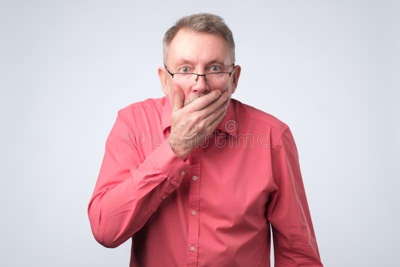 Mannen i röd skjorta med handen över hans mun, bedövade royaltyfri fotografi