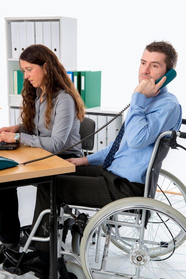 Mannen i rullstol och hans är den kvinnliga kollegan som arbetar i joen royaltyfria bilder