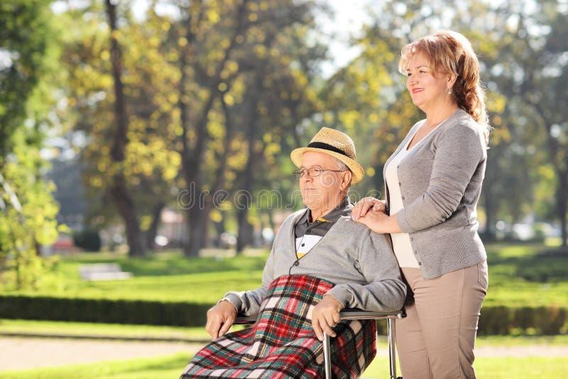 Mannen i rullstolsammanträde med hans fru parkerar in royaltyfri fotografi
