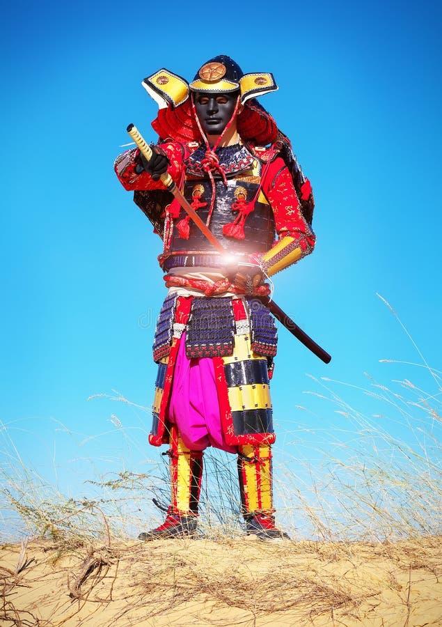 Mannen i samurajdräkt drar ut hans kraftiga varma svärd royaltyfria foton