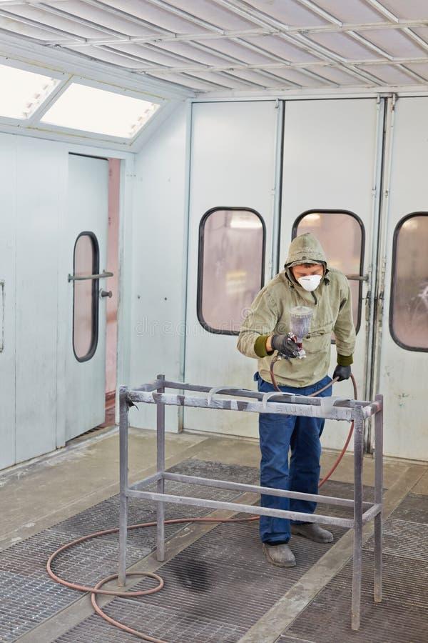 Mannen i skyddande kläder arbetar i målarfärg-bespruta bås royaltyfria foton