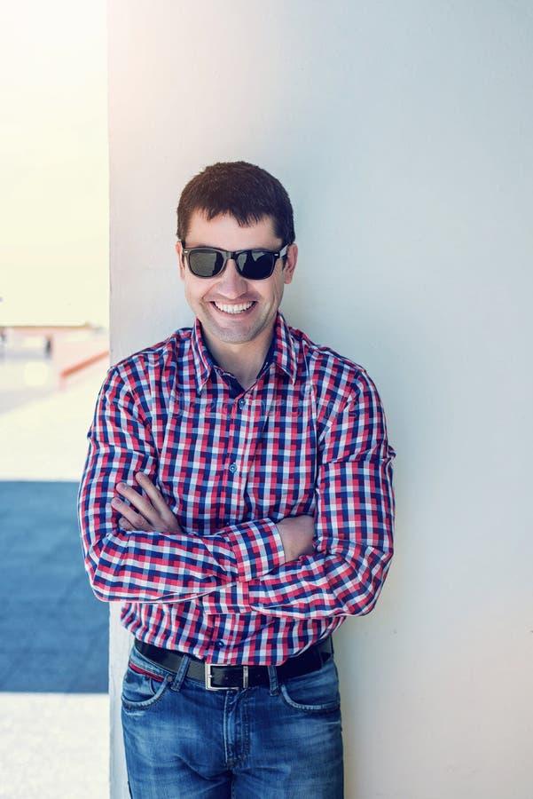 Mannen i sommaren mot väggen, exponeringsglasen, den lyckliga leende-, bärajeansen och en skjorta, ljus solig dag Idénollan royaltyfri fotografi