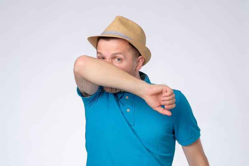 Mannen i sommarhatt har den körande näsan, gnider näsan med armen och att vara dåligt royaltyfri bild