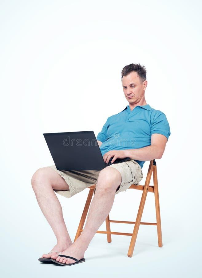 Mannen i sommarkläder sitter på en stol som skriver på en bärbar dator Ljus bakgrund Begrepp av arbete på semester royaltyfri fotografi