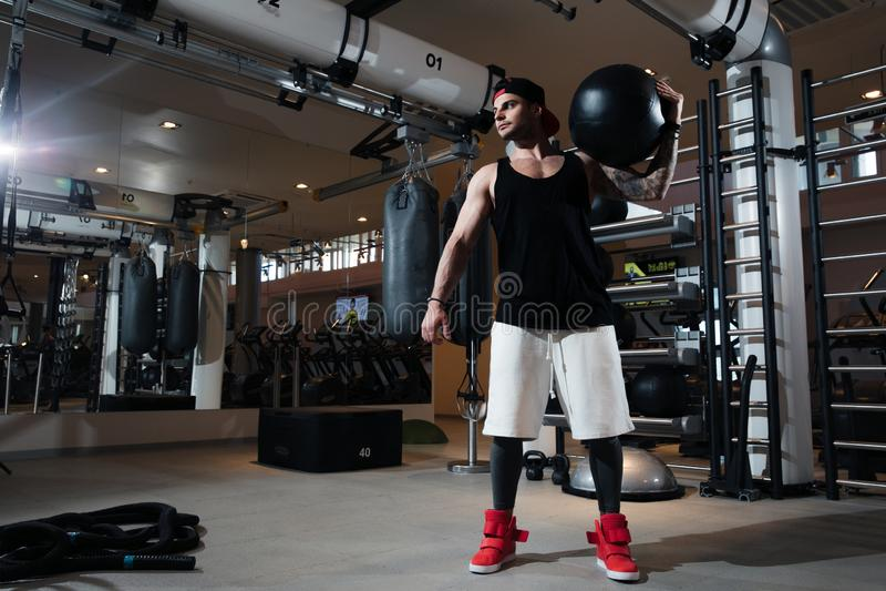 Mannen i sportswear utbildar i idrottshallen arkivbilder