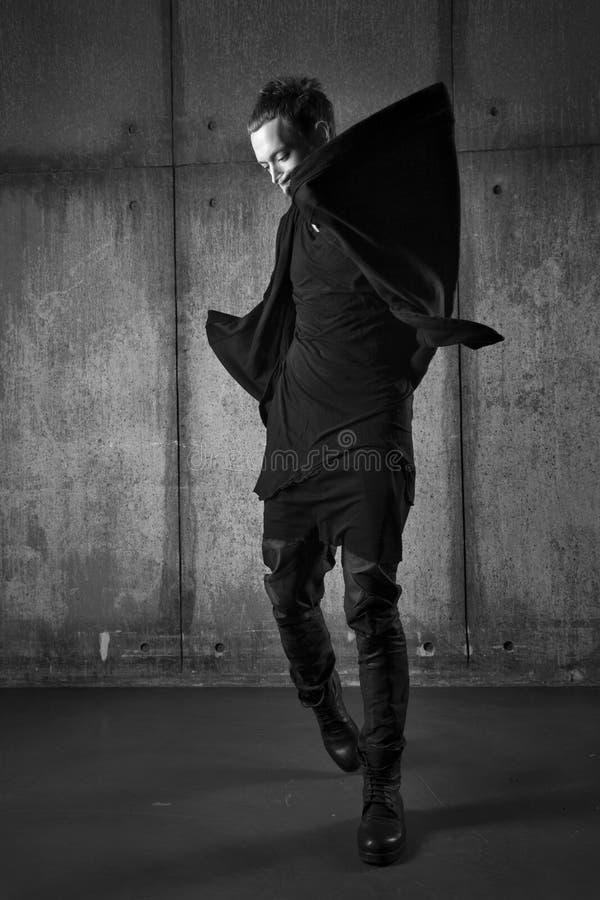 Mannen i svart mörkerkläder, ilar mode royaltyfri fotografi