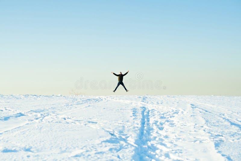 Mannen i varm tröja med ett skägg går på gatan i vintern i en varm solig dag på floden arkivfoto