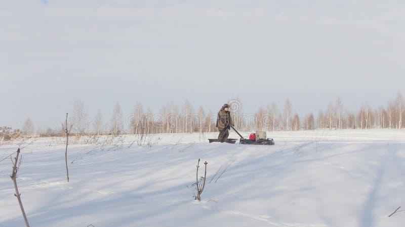 Mannen i vinterkläder fastar ridningen och manövrera på mini- snövessla på djupa snödrivor arkivfoto