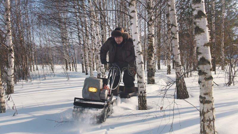 Mannen i vinterkläder fastar ridningen på mini- snövessla på djupa snödrivor i skogen och att manövrera mellan träden royaltyfri fotografi