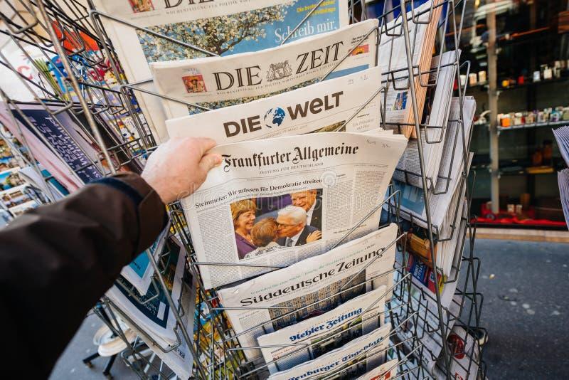 Mannen inhandlar en Frankfurter Allgemeine Zeitung tidning från pr royaltyfri fotografi