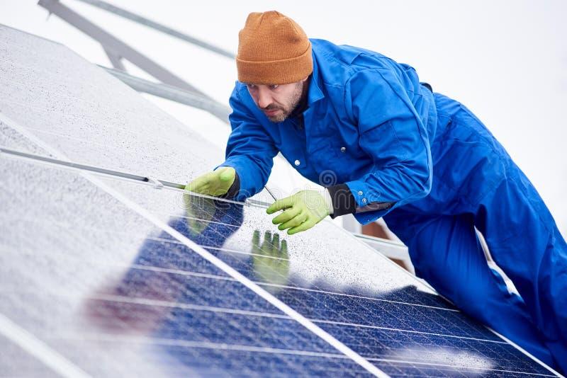 Mannen installerar sol- batterier genom att använda hjälpmedel på taket i vinter royaltyfria foton