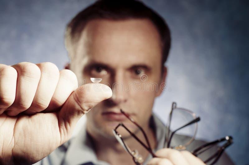 Mannen jämför kontaktlinsen med exponeringsglas fotografering för bildbyråer