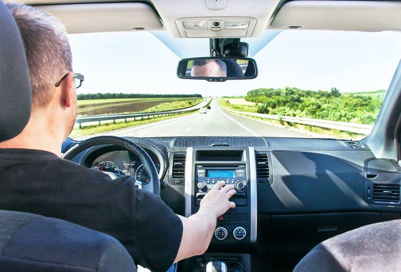 Mannen justerar solid volym i bilstereon (radion) royaltyfri foto