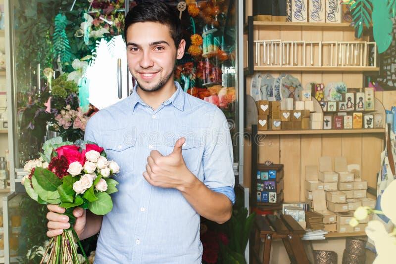 Mannen köper blommor på en blomsterhandel rymma en bukett i hand royaltyfria bilder