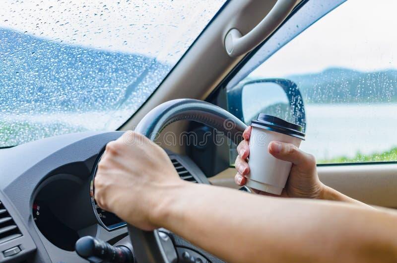 Mannen kör en bil och dricker ett varmt kaffe i takeaway kopp I royaltyfri bild