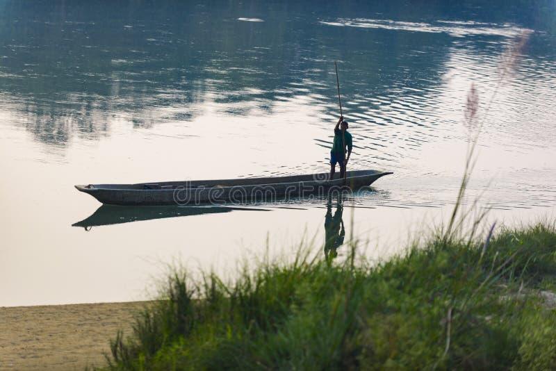 Mannen kör ett träfartyg på floden, Nepal, den Chitwan nationalparken, royaltyfria foton