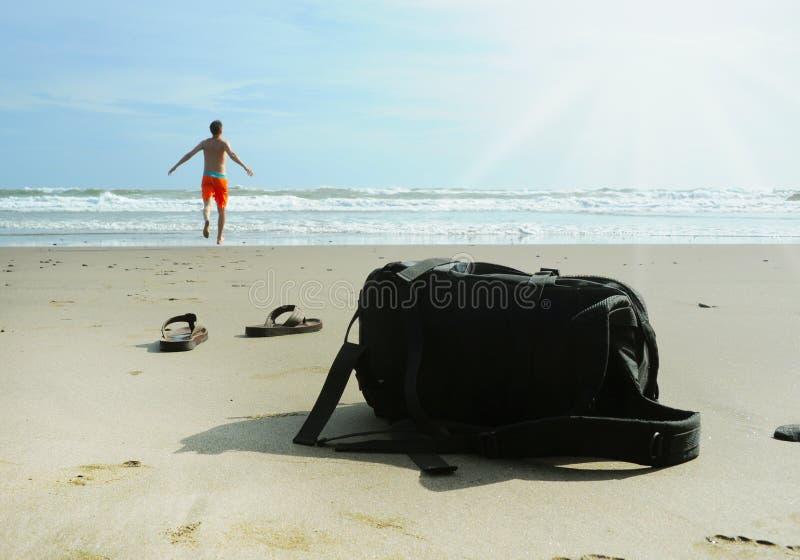 Mannen kör in i havet för att simma fotografering för bildbyråer
