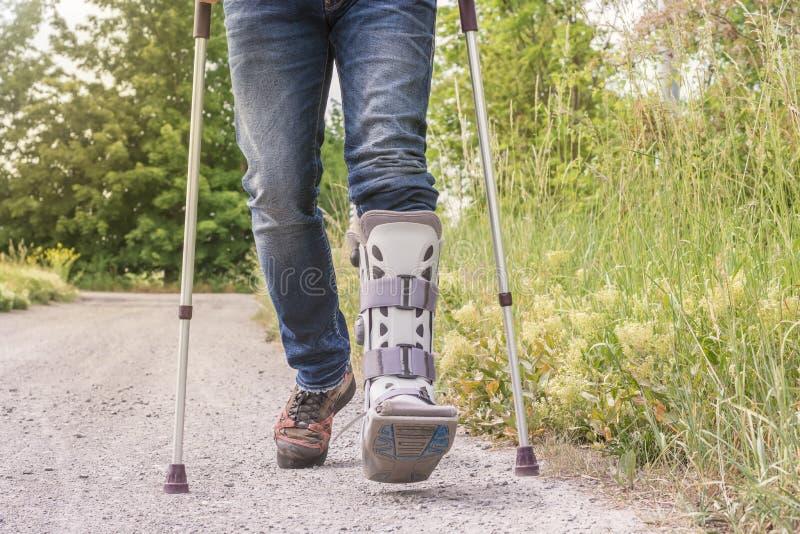 Mannen kör med en orthosis och går hjälpmedel på en grusväg royaltyfria foton