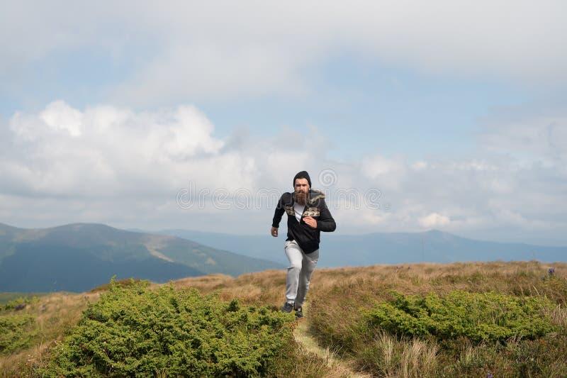 Mannen kör på grön äng i berg på molnig himmel royaltyfria foton