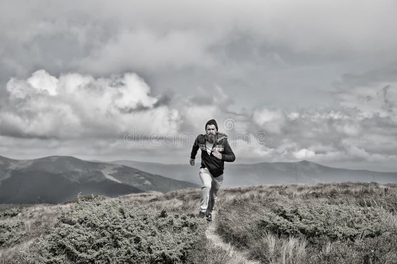 Mannen kör på grön äng i berg på molnig himmel arkivbilder