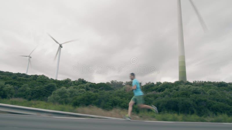 Mannen kör snabbt längs vägen mot fungerande vindgeneratorer arkivfoton