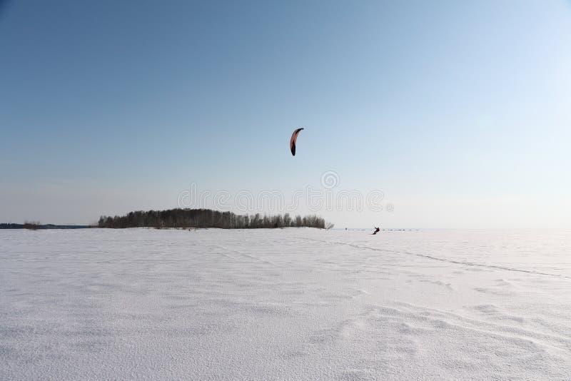 Mannen kiting på skidar på den djupfrysta floden arkivbild