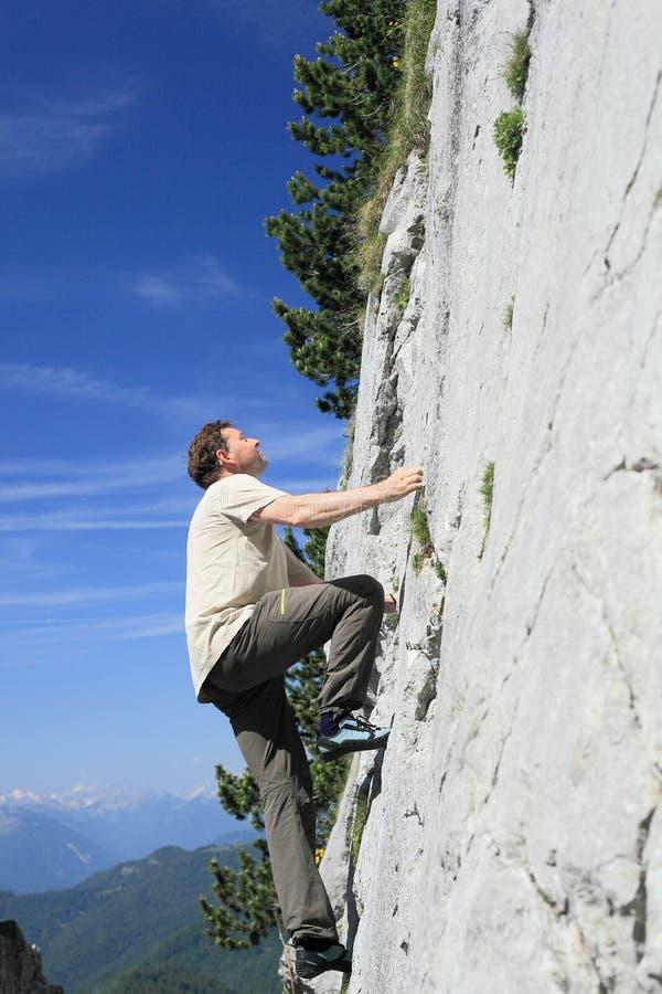 Mannen klättrar på vaggar väggen arkivfoton