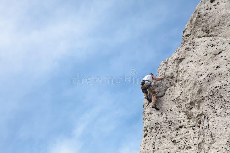 Mannen klättrar till överkanten av berget Vagga klättringen med säkring royaltyfri bild