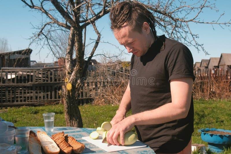 Mannen klipper en zucchini i trädgården arkivbilder