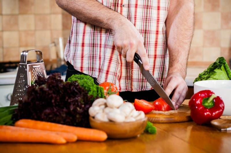 Mannen klipper nya vårgrönsaker royaltyfri foto